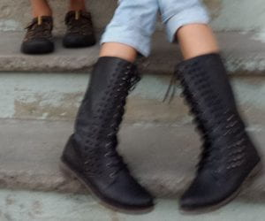Kids sitting on porch, only their shoes is seen